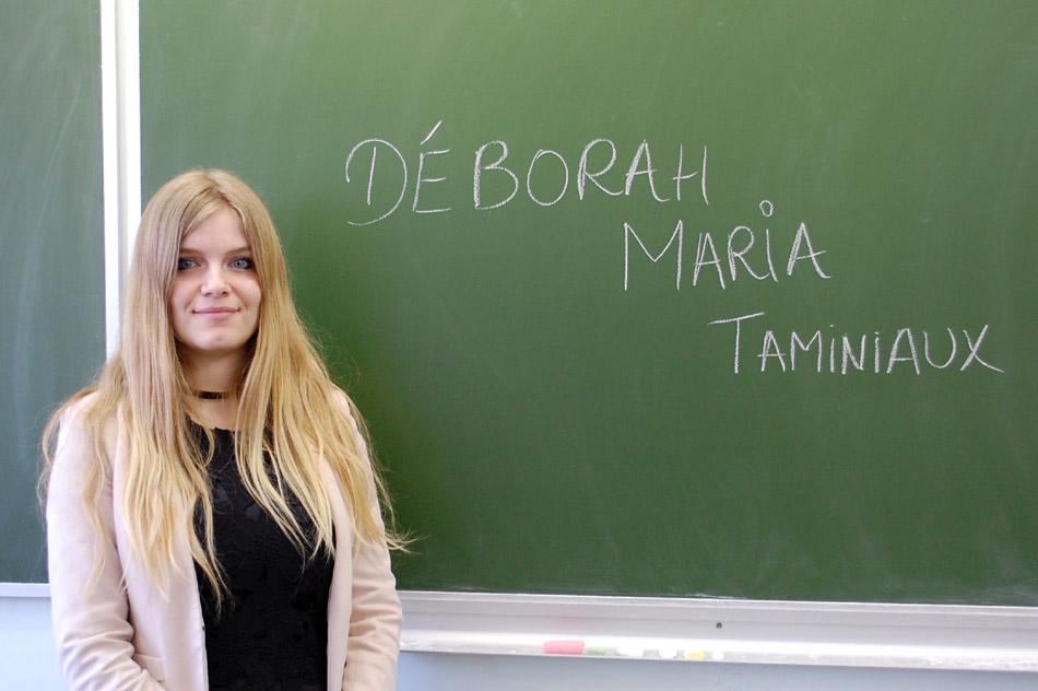 Дебора Мария Таминьё на фоне доски