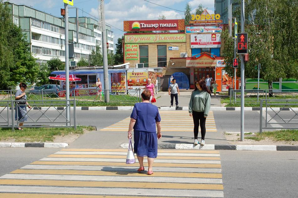 Пожилая женщина переходит улицу Гагарина в городе Обнинске на красный свет