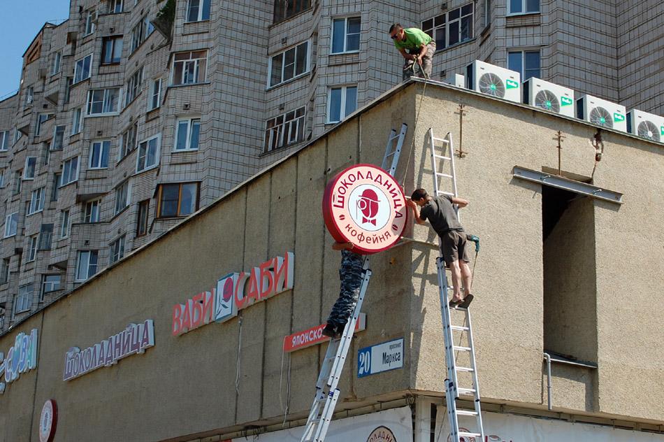 Рабочие крепят логотип кофейни «Шоколадница» на фасад здания в городе Обнинске (2 августа 2017 года)